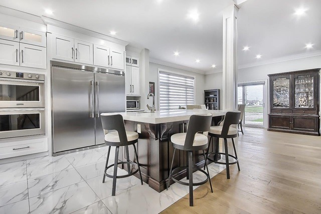 Spacious kitchen with shaker white cabinets with an island made of beech espresso base cabinets. The countertops are a marble-like quartz.